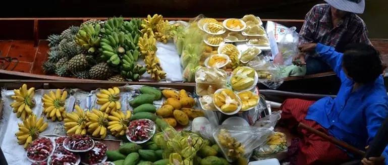 Bootje met verkopers van Aziatische vruchten