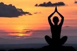 Mediterend mens bij zonsondergang