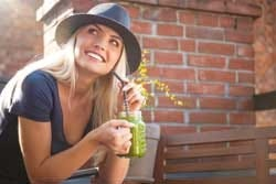 Frisse vrouw met groene smoothie