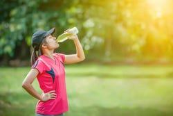 Vrouw drinkt flesje sportdrank
