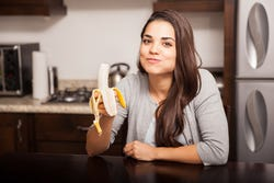 Leuk meisje dat smakelijk een banaan eet