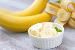 Bananen in schil en schaaltje gesneden banaan
